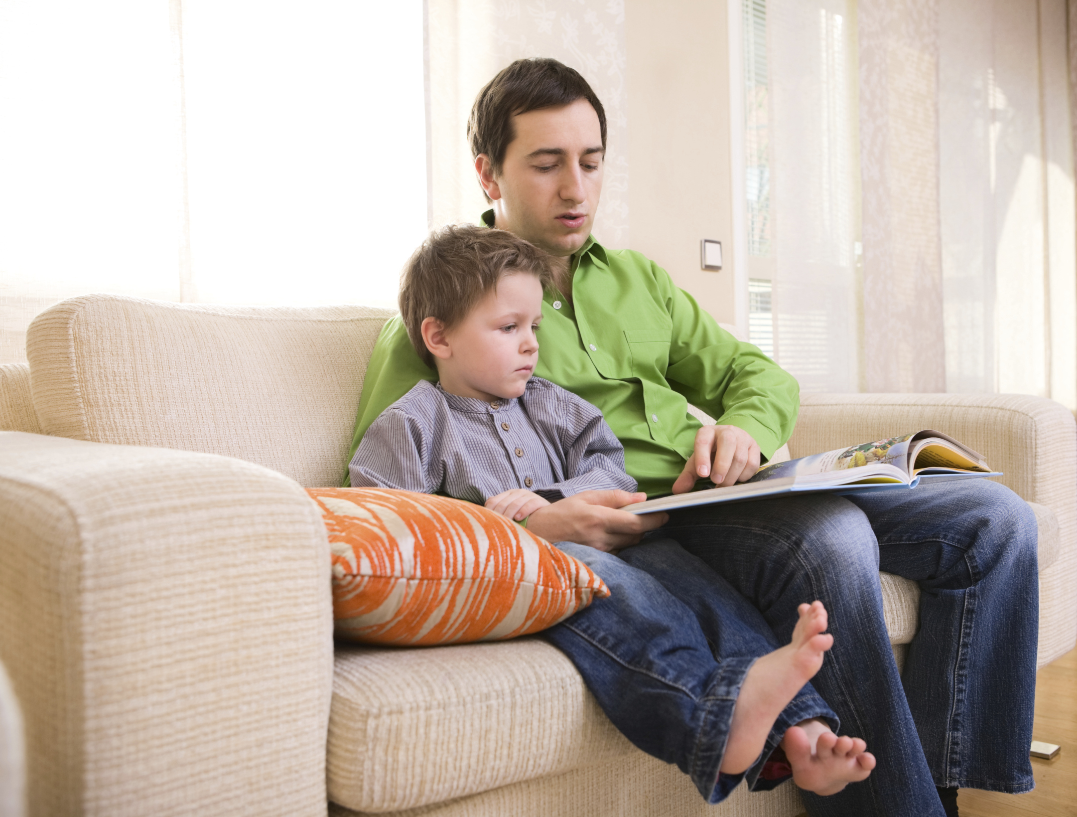 Father and son reading book together at home